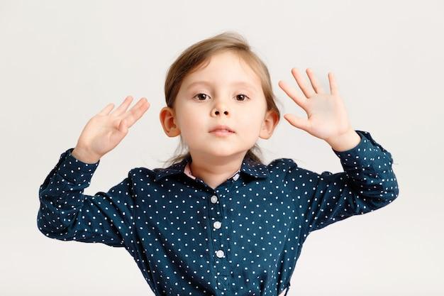 Piccola fashion girl caucasica di 46 anni che indossa un abito blu a pois in piedi con la mano alzata
