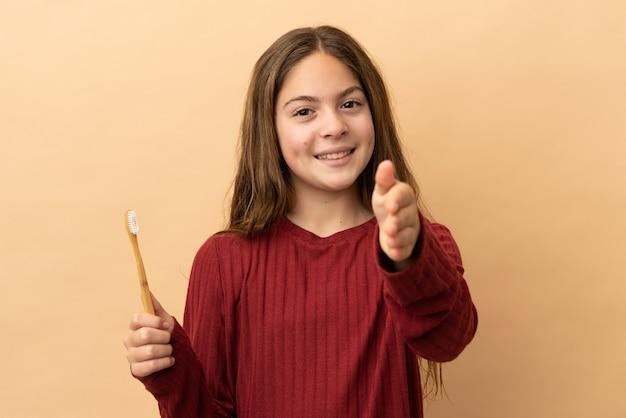 Piccola ragazza caucasica che si lava i denti isolati su sfondo beige che stringe la mano per chiudere un buon affare
