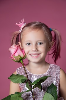 Piccola ragazza caucasica in abito festivo con paillettes in posa con fiore di rosa su sfondo rosa che guarda la telecamera
