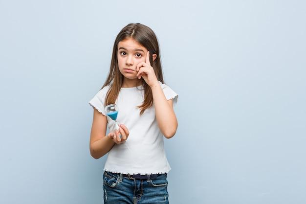 La piccola ragazza caucasica che tiene una clessidra che indica il suo tempio con il dito, pensando, si è concentrata su un compito.