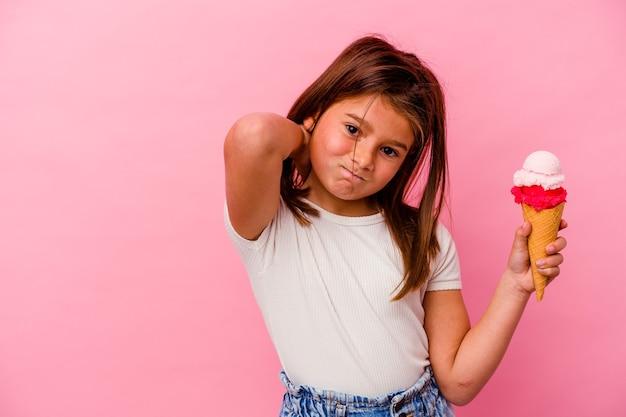 Piccola ragazza caucasica con gelato isolato su sfondo rosa che tocca la parte posteriore della testa, pensa e fa una scelta.