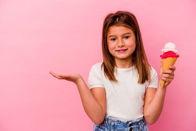 Piccola ragazza caucasica che tiene il gelato isolato sul colore rosa che mostra uno spazio della copia su una palma e che tiene un'altra mano sulla vita.