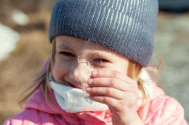 Piccola ragazza caucasica che tiene un pezzo di ghiaccio trasparente contro il suo occhio.