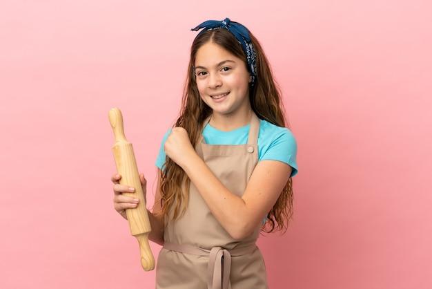 Piccola ragazza caucasica che tiene un mattarello isolato su sfondo rosa che celebra una vittoria