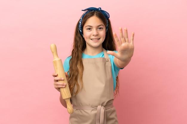 Piccola ragazza caucasica che tiene un mattarello isolato su sfondo rosa contando cinque con le dita