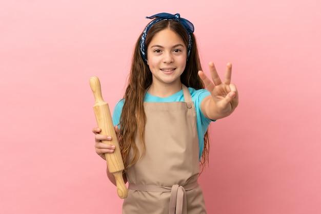 Piccola ragazza caucasica che tiene un mattarello isolato su sfondo rosa felice e conta tre con le dita