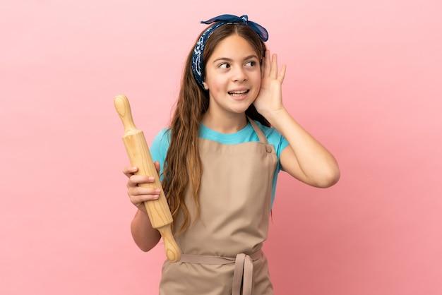 Piccola ragazza caucasica che tiene un mattarello isolato su sfondo rosa ascoltando qualcosa mettendo la mano sull'orecchio