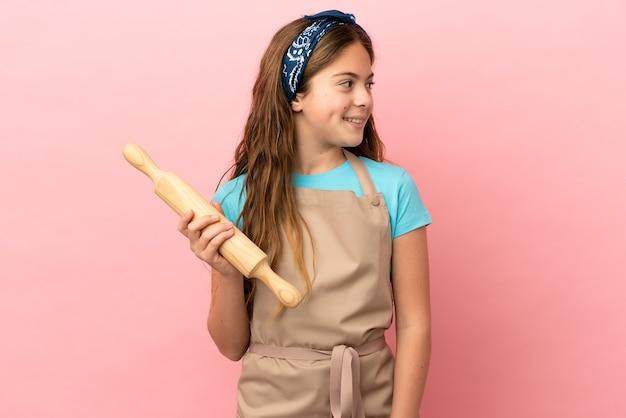 Piccola ragazza caucasica che tiene un mattarello isolato su sfondo rosa che guarda di lato