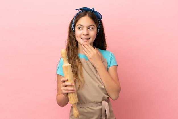Piccola ragazza caucasica che tiene un mattarello isolato su sfondo rosa che guarda in alto mentre sorride