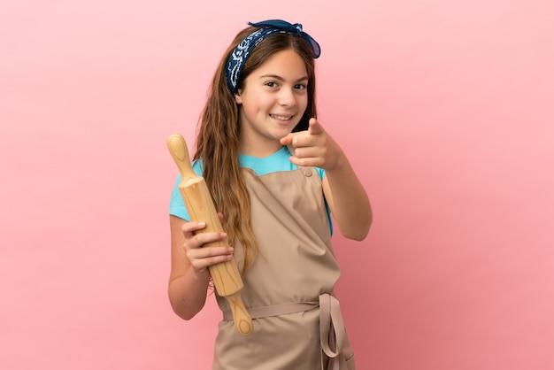 Piccola ragazza caucasica che tiene un mattarello isolato su sfondo rosa che punta davanti con espressione felice
