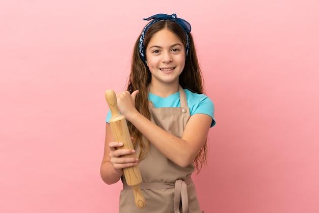 Piccola ragazza caucasica che tiene un mattarello isolato su sfondo rosa orgoglioso e soddisfatto di sé