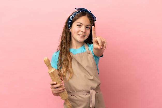Piccola ragazza caucasica che tiene un mattarello isolato su sfondo rosa che mostra e solleva un dito