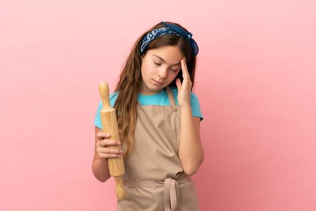 Piccola ragazza caucasica che tiene un mattarello isolato su sfondo rosa con mal di testa