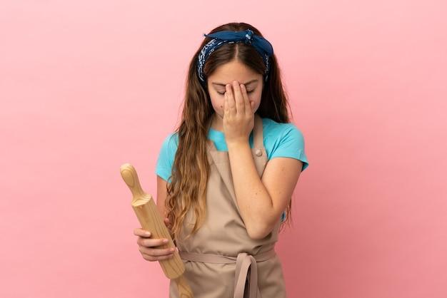 Piccola ragazza caucasica che tiene un mattarello isolato su sfondo rosa con espressione stanca e malata