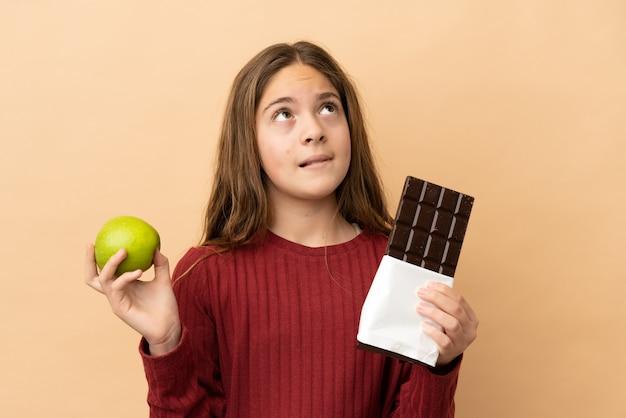 Piccola ragazza caucasica isolata su sfondo beige che ha dei dubbi mentre prende una tavoletta di cioccolato in una mano e una mela nell'altra