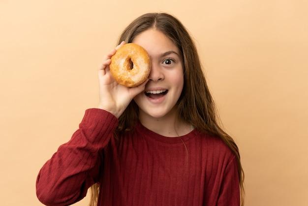Piccola ragazza caucasica isolata su fondo beige che tiene una ciambella in un occhio