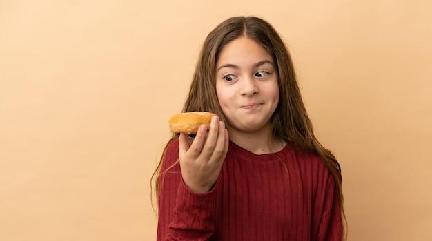 Piccola ragazza caucasica isolata su fondo beige che tiene le ciambelle