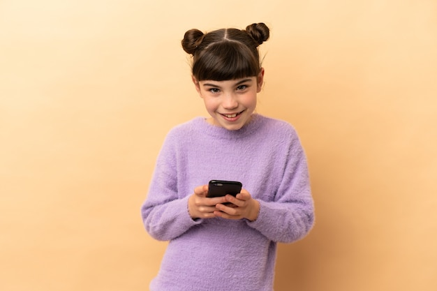 Piccola ragazza caucasica isolata sul beige inviando un messaggio con il cellulare