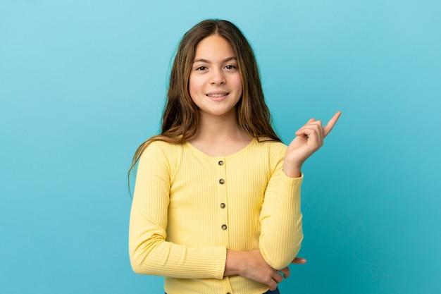 Piccola ragazza caucasica isolata su sfondo blu felice e rivolta verso l'alto