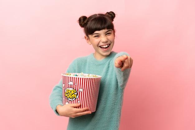 Piccola ragazza caucasica isolata tenendo un grande secchio di popcorn mentre indica la parte anteriore