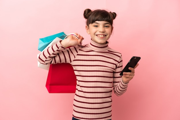 La piccola ragazza caucasica ha isolato i sacchetti della spesa della tenuta e la scrittura di un messaggio