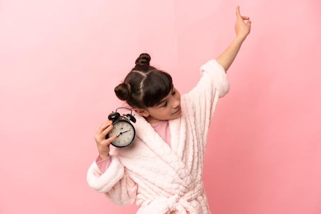 Piccola ragazza caucasica isolata in pigiama e tenendo l'orologio con l'espressione felice