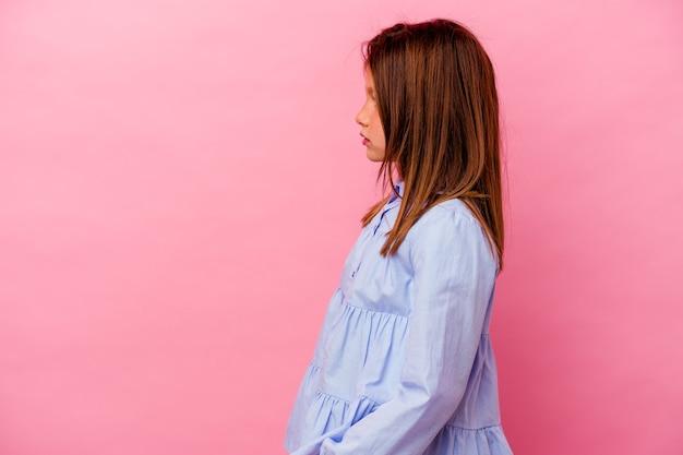 Piccola ragazza caucasica isolata su sfondo rosa guardando a sinistra, posa laterale.