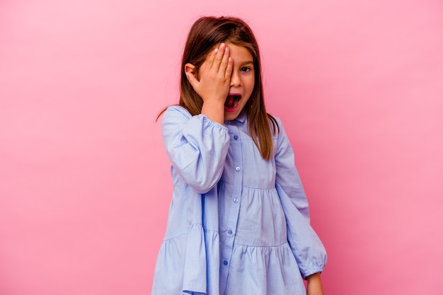 Piccola ragazza caucasica isolata su sfondo rosa divertendosi coprendo metà del viso con il palmo.