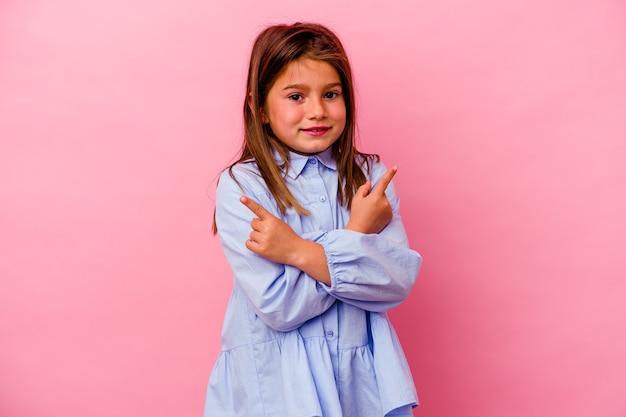 La piccola ragazza caucasica isolata su sfondo rosa punta lateralmente, sta cercando di scegliere tra due opzioni.