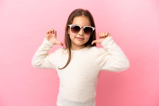 Piccola ragazza caucasica isolata su sfondo rosa orgogliosa e soddisfatta di sé