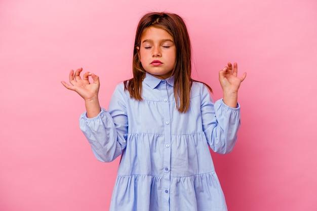 La piccola ragazza caucasica isolata su sfondo rosa si rilassa dopo una dura giornata di lavoro, sta eseguendo yoga.