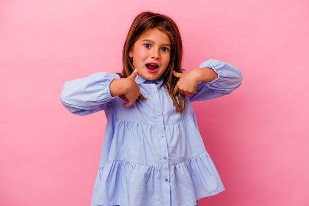 La piccola ragazza caucasica isolata su fondo rosa ha sorpreso indicando con il dito, sorridendo ampiamente.