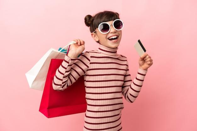 Piccola ragazza caucasica isolata sui sacchetti della spesa rosa della tenuta e una carta di credito