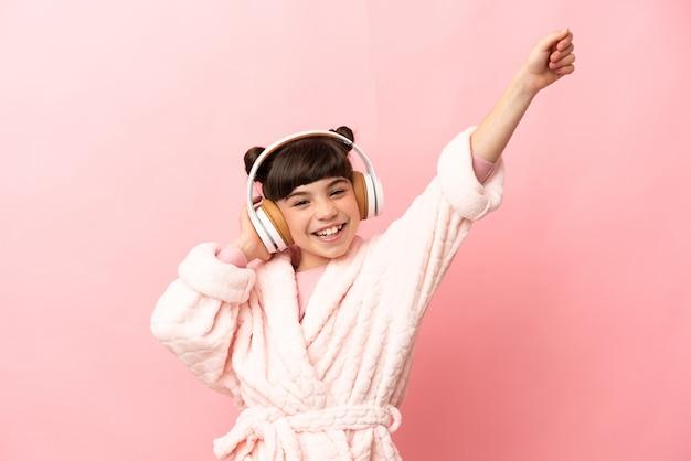 Piccola ragazza caucasica isolata sul rosa in pigiama e che tiene un cuscino e ascoltare musica