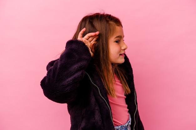 Piccola ragazza caucasica isolata sul colore rosa che prova ad ascoltare un pettegolezzo.