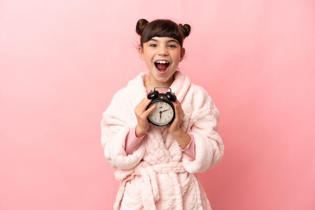 Piccola ragazza caucasica isolata sulla parete rosa in pigiama e tenendo l'orologio con espressione sorpresa