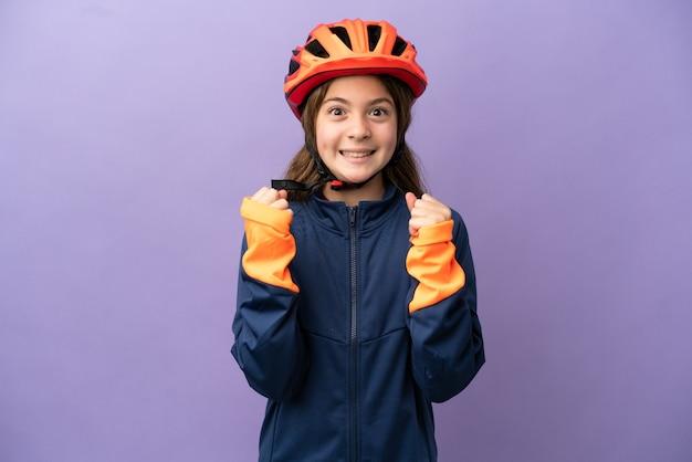 Piccola ragazza caucasica isolata su sfondo viola che celebra una vittoria nella posizione del vincitore