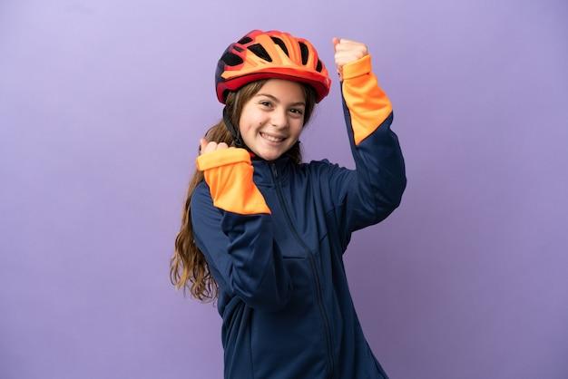 Piccola ragazza caucasica isolata su sfondo viola che celebra una vittoria