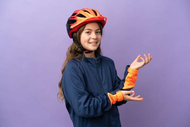 Piccola ragazza caucasica isolata su sfondo viola che allunga le mani di lato per invitare a venire