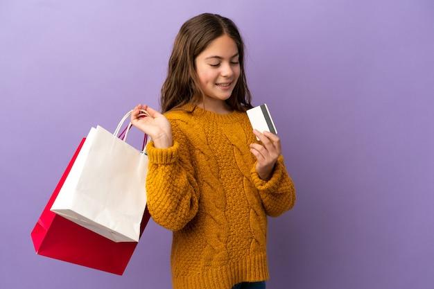 Piccola ragazza caucasica isolata su sfondo viola con borse della spesa e una carta di credito