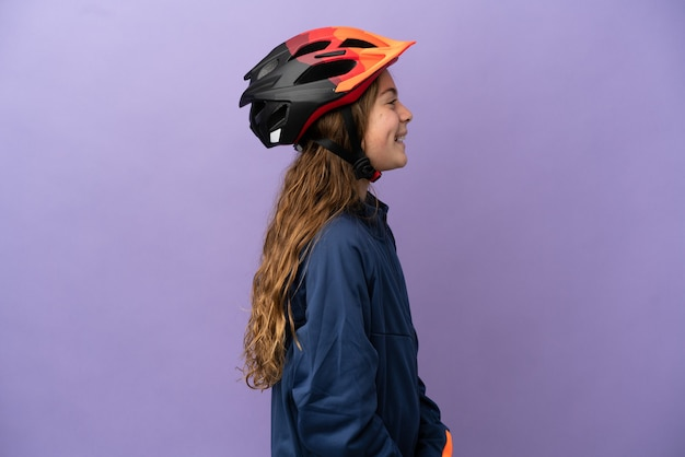 Piccola ragazza caucasica isolata su sfondo viola che ride in posizione laterale