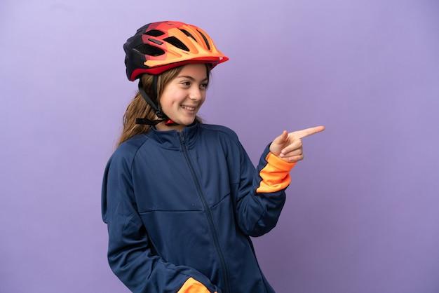 Piccola ragazza caucasica isolata su sfondo viola che punta il dito di lato e presenta un prodotto