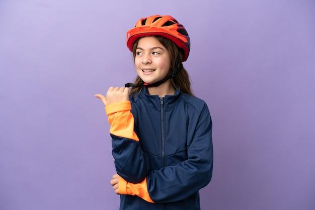 Piccola ragazza caucasica isolata su sfondo viola che punta al lato per presentare un prodotto