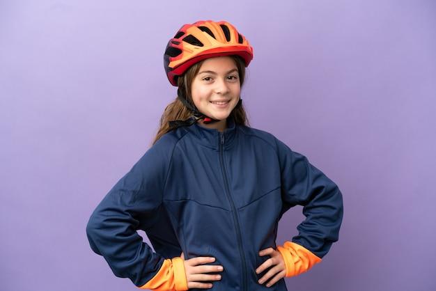 Piccola ragazza caucasica isolata su sfondo viola in posa con le braccia all'anca e sorridente