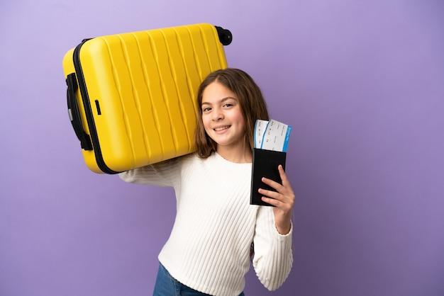 Piccola ragazza caucasica isolata su sfondo viola in vacanza con valigia e passaporto