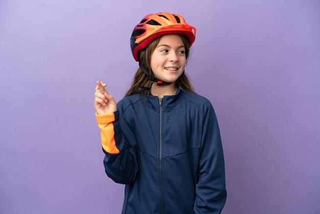 Piccola ragazza caucasica isolata su sfondo viola con le dita incrociate e augurando il meglio