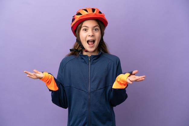 Piccola ragazza caucasica isolata su sfondo viola con espressione facciale scioccata