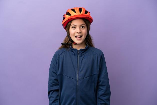Piccola ragazza caucasica isolata su sfondo viola con espressione facciale a sorpresa