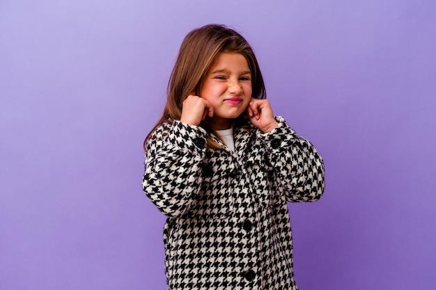Piccola ragazza caucasica isolata sulle orecchie viola della copertura con le mani.