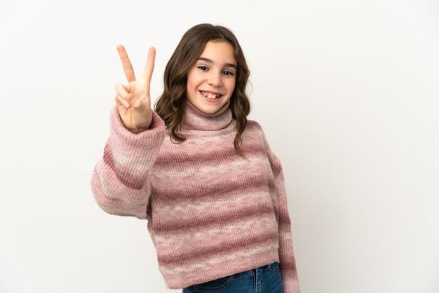 Piccola ragazza caucasica isolata sulla parete bianca che sorride e che mostra il segno di vittoria